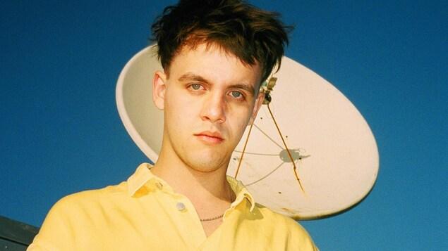 Le chanteur Les Louanges (Vincent Roberge), vêtu d'un polo jaune, se tient devant une antenne parabolique et un ciel bleu.