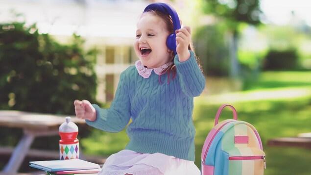 Une fillette souriante avec un des écouteurs, à côté de son sac à dos assise sur une table à pique-nique présumément dans une cour d'école.