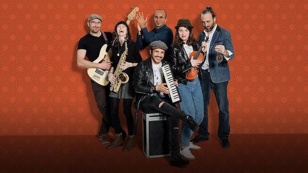 Le groupe de musiciens pose sur un fond orange avec leurs instruments.