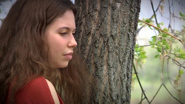 La jeune artiste Amélie Tétrault se tient proche d'un arbre.
