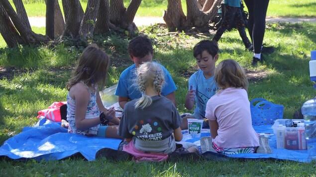 Les enfants font des activités d'école assis sur une pelouse dehors.