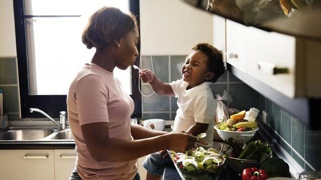 Dans une cuisine, un jeune garçon porte une cuillère à la bouche de sa mère, qui prépare une salade.