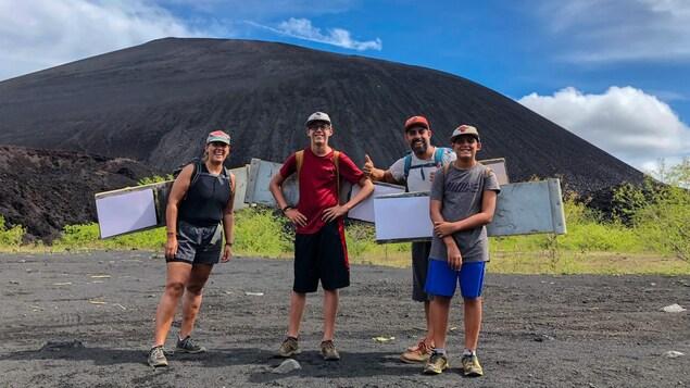 Un couple dans la trentaine et ses deux fils, portant chacun une casquette, devant le volcan Cerro Negro, au Nicaragua.
