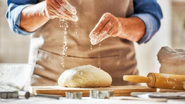 Une personne fait son propre pain sur un plan de travail.