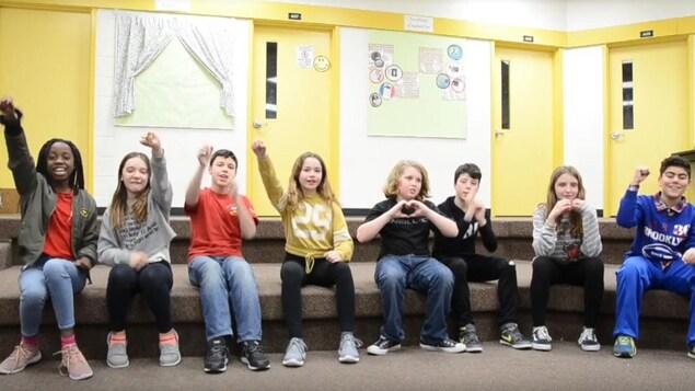 Des élèves assis face à la caméra déclament leur texte slame.