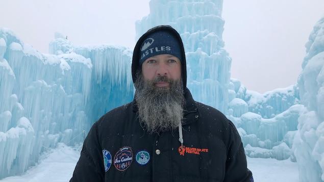 quadragenaire vêtu d'un parka devant un mur de glace