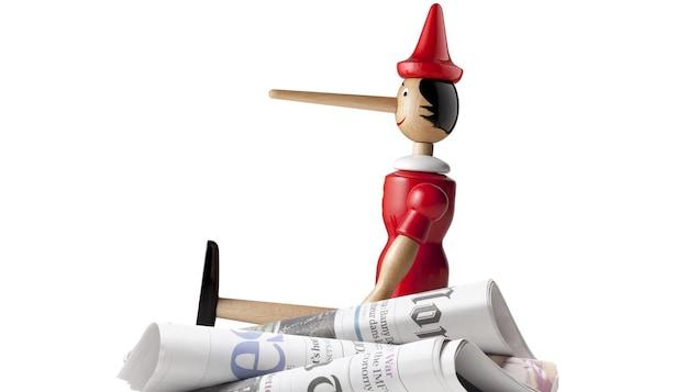 Un Pinocchio assis sur une pile de journaux pour représenté les Fake News.