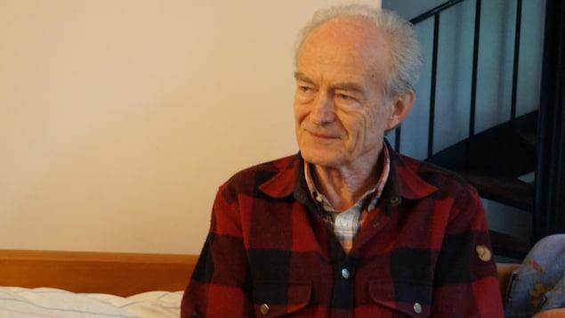 Jean Meyer en entrevue assis avec une chemise carreautée le visage en bias.