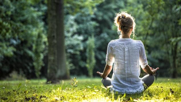 Une femme qui médite dans un parc