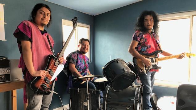 Les trois musiciens portent des vêtements traditionnels pendant qu'ils pratiquent.