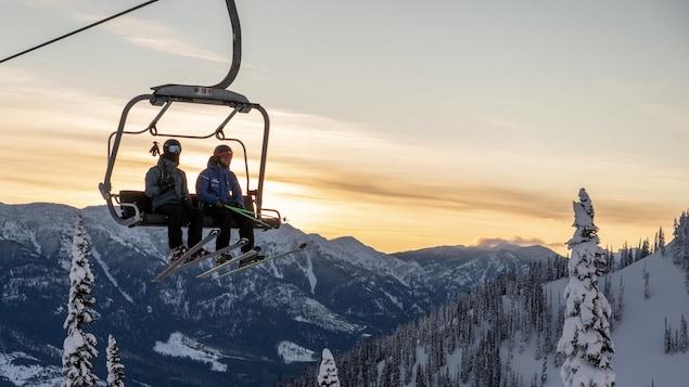 Deux skieurs dans un monte-pente dans les montagnes de Fernie en Colombie-Britannique