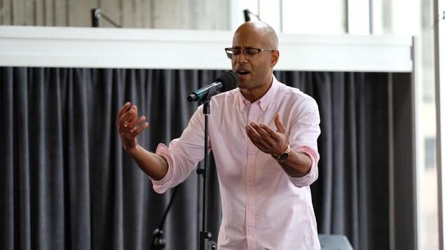 Un homme chante devant un micro