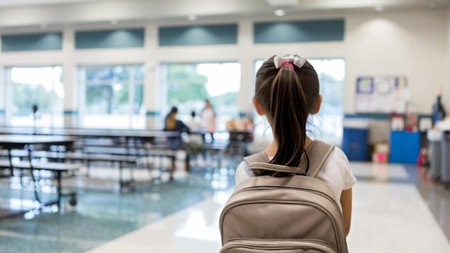 Une petite fille avec un sac à dos vue de dos alors qu'elle entre dans la cafétéria d'une école.