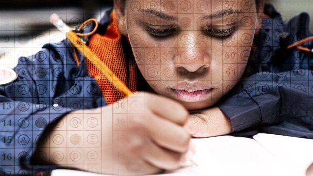 Un jeune, crayon à la main, remplit les pages d'une test scolaire.