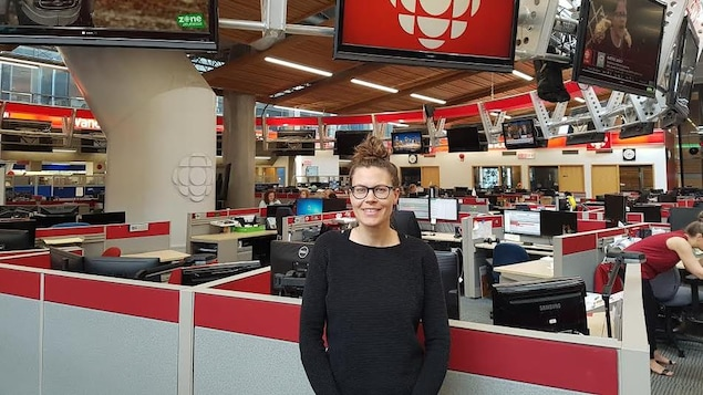 Une femme est photographiée dans une salle de nouvelles.