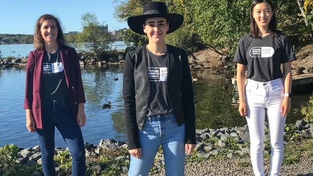 Trois jeunes femmes sourient devant un lac à Sudbury en portant les chandails de Futur du Nord.