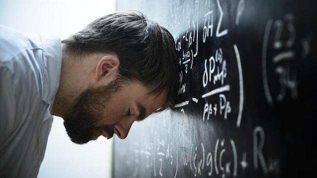 Un étudiant se frappe la tête contre un tableau où figurent de nombreuses équations scientifiques.