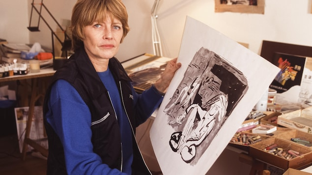 Claire Bretecher tenant l'une de ses œuvres.