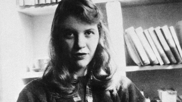 L'auteure Sylvia Plath, assise devant une bibliothèque.