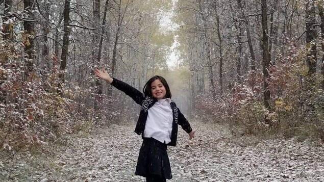 Isabelle d'Eschambault, jeune actrice de 11 ans. Elle est au milieu d'un sentier bordé d'arbres.