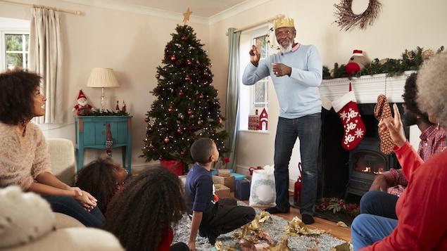 Dans un salon décoré pour Noël, une famille de 7 personnes joue à un jeu de société. Le grand-père est debout et semble mimer un mot.