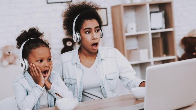 Une mère et son enfant regardent un écran d'ordinateur avec grande surprise. Elles écoutent un contenu audio.