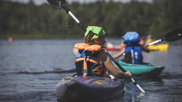 Des enfants font du kayak sur un lac.