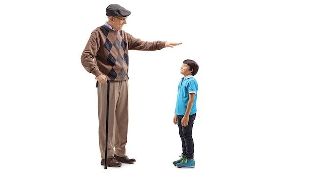 Un homme âgé mesure la taille d'un enfant à l'aide de sa main.