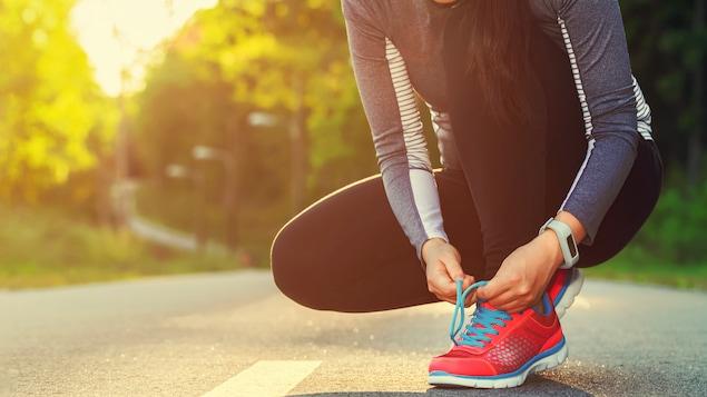 Une femme se prépare à courir en laçant ses chaussures.