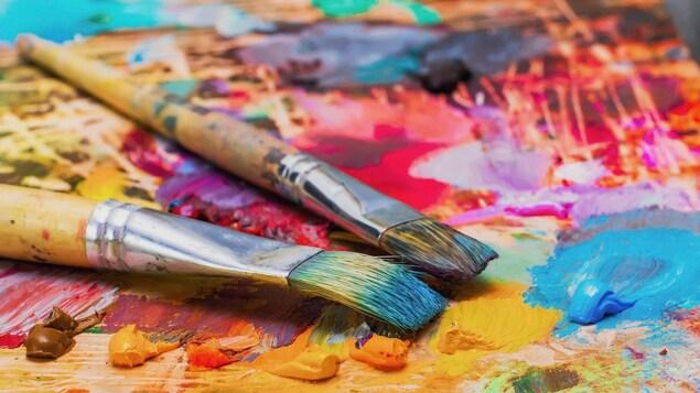 Des pinceaux se trouvent sur la palette d'un artiste.
