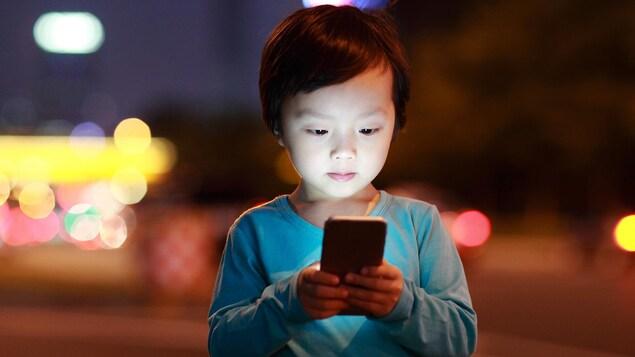 Un bambin est captivé par l'écran d'un téléphone portable.
