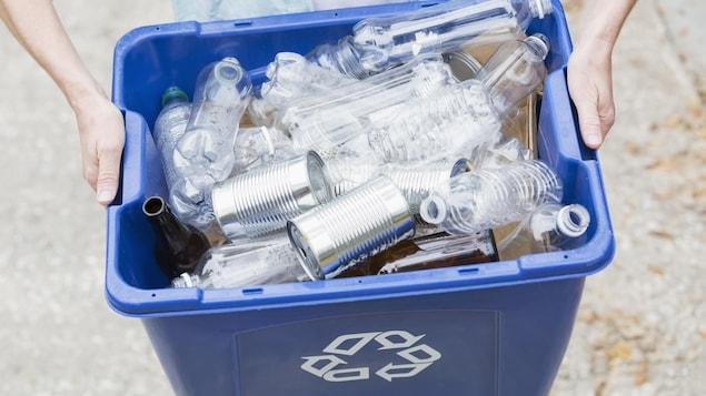 Une personne tient un bac de recyclage bleu rempli de bouteilles de plastique vides.