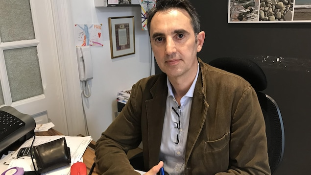 Un homme assis à son bureau regarde la caméra.