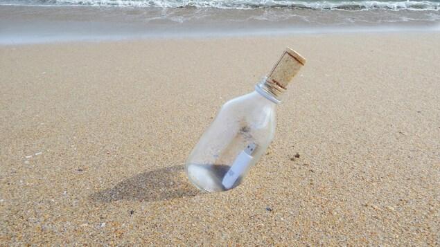 Une clé USB dans une bouteille en verre sur une plage.