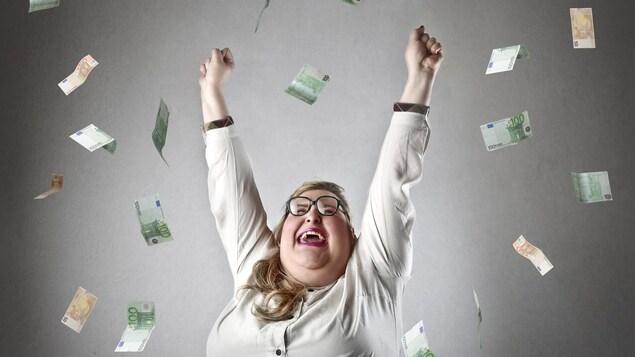 Une femme lève les bras en guise de célébration tandis que des billets de banque lui pleuvent dessus.