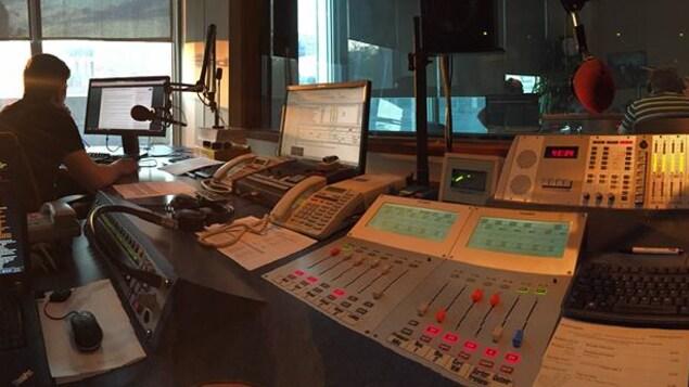 Une salle de contrôle radio, de gauche à droite : un homme vu de dos travail à un ordinateur. Et une console de radio avec le studio radio en arrière-plan.