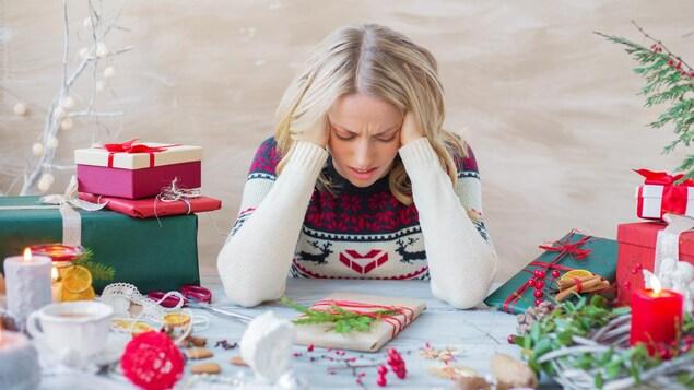 Une femme se tient la tête dans les mains, entourée de cadeaux de Noël.