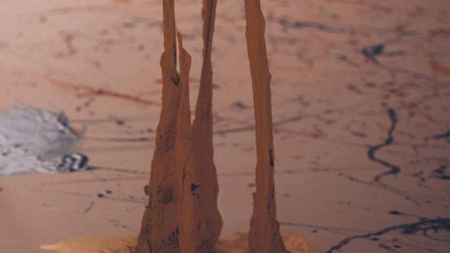 Photo d'une sculpture abstraite en forme de stalagmite et d'éclats de peinture dans une pièce.