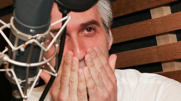 L'animateur Olivier Niquet dans un studio de radio, les mains sur la bouche comme s'il était outré.