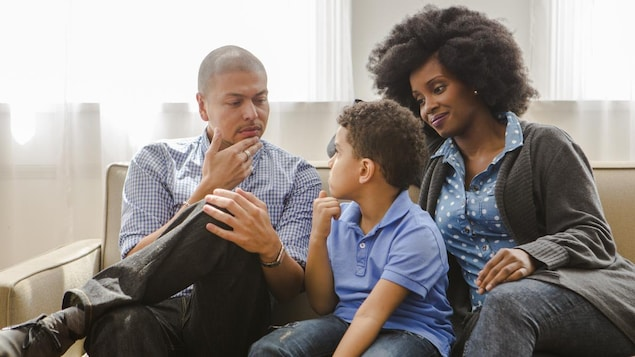 Un homme, un enfant et une femme discutent, assis sur un canapé.