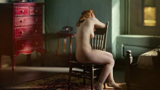 Une femme nue est assise sur une chaise, de dos, dans un appartement en ville. Elle a de longs cheveux roux et elle ressemble à Vénus, déesse de l'antiquité grecque. Elle regarde en direction d'une fenêtre, qui offre une vue sur un édifice brun. La scène ressemble plus à une peinture qu'une photo