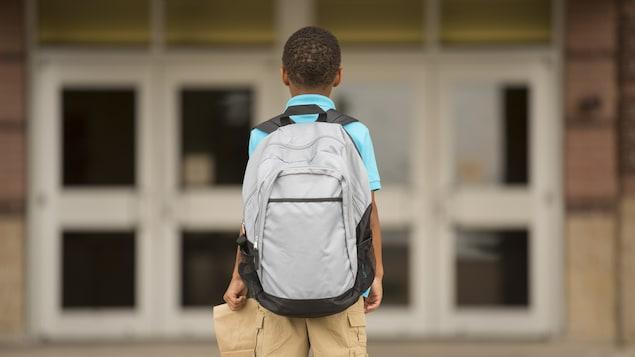 Un garçon regarde les portes d'une école.