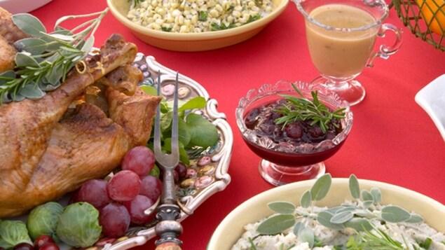 Sur une table avec une nappe rouge de Noël, on voit une dinde rôtie, une sauce aux canneberges et une salade de poulet.