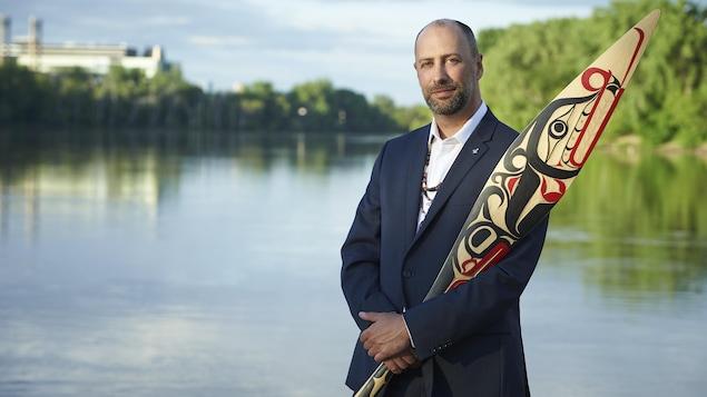 Ry Moran tient un oeuvre d'arts près d'une rivière.