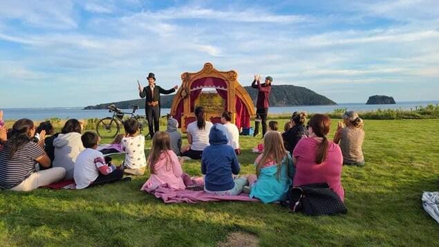 Deux comédiens avec une petite scène, derrière eux, la mer, et devant eux, des spectateurs assis.