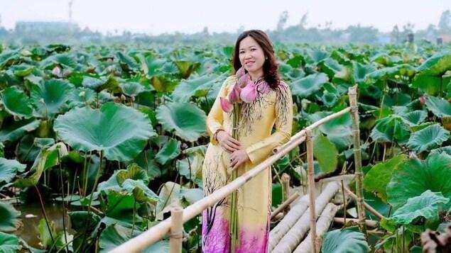 Une femme debout au milieu de la végétation.