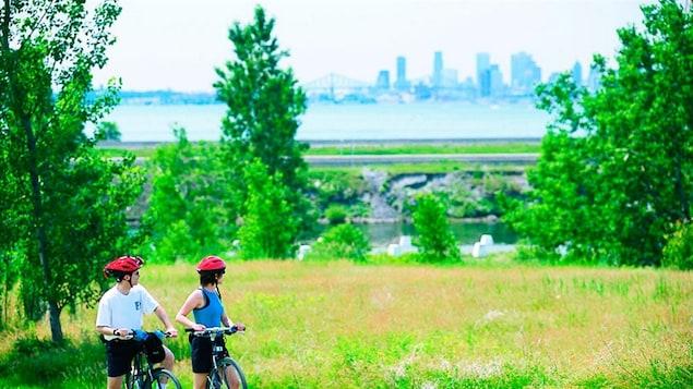 Deux cyclistes au parc national des Îles-de-Boucherville. On aperçoit la ville de Montréal et le pont Jacques-Cartier au loin.