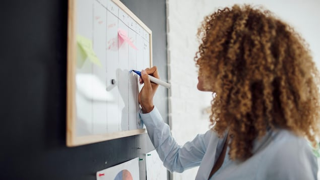 Une femme de profil est en train d'écrire son horaire sur un tableau.