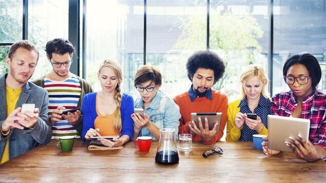 Sept jeunes ayant chacun en main une tablette ou en cellulaire.