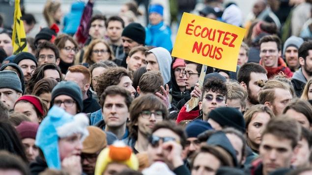Une foule de protestataires dont l'un tient une pancarte sur laquelle il est écrit «Écoutez-nous».